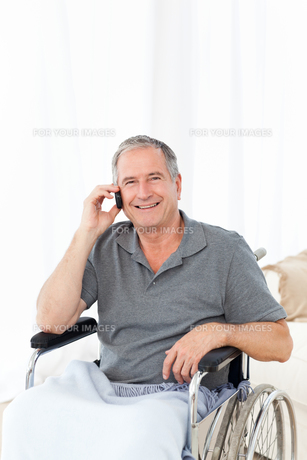 Senior in his wheelchair phoningの素材 [FYI00483491]