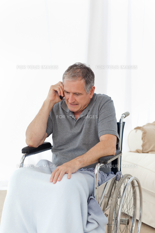 Senior in his wheelchair phoningの素材 [FYI00483493]