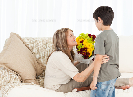 Boy offering flowers to his motherの写真素材 [FYI00483522]
