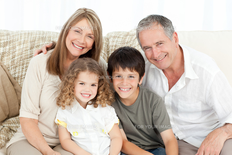 A happy family on their sofa looking at the cameraの写真素材 [FYI00483527]