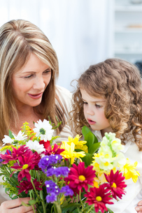 Grandmother with a little girl taking flowersの写真素材 [FYI00483532]