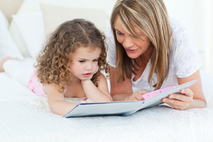 Young girl reading a book with her grandmotherの写真素材 [FYI00483539]