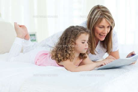 Young girl reading a book with her grandmotherの素材 [FYI00483541]