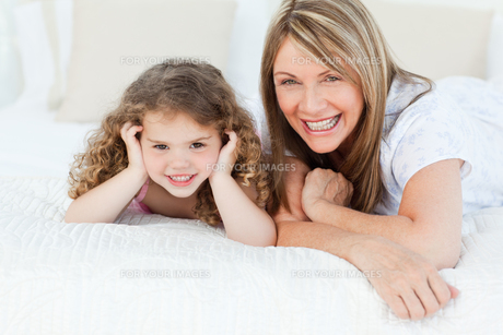 Little girl with her mother looking at the camera while lying on a bedの写真素材 [FYI00483546]