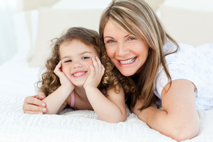 Little girl with her mother looking at the camera while lying on a bedの写真素材 [FYI00483547]