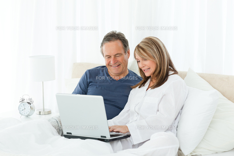 Mature lovers looking at their laptopの写真素材 [FYI00483569]