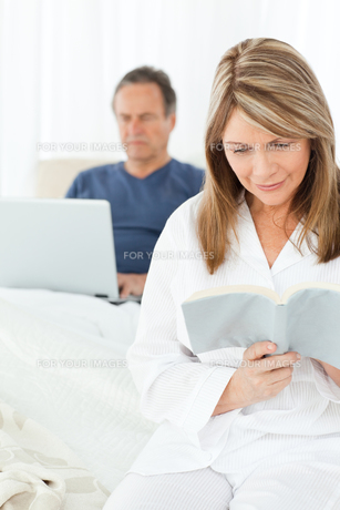 Man looking at his laptop while her wife is readingの写真素材 [FYI00483572]