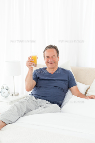 Retired man looking at the camera while he is drinking oranje juiceの写真素材 [FYI00483573]