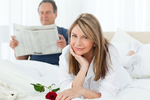 Happy woman with her rose while her husband is reading a newspaperの素材 [FYI00483576]