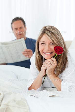 Happy woman with her rose while her husband is reading a newspaperの素材 [FYI00483577]