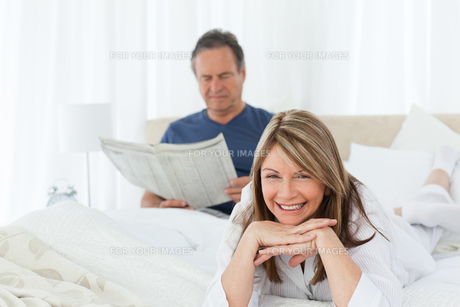 Smiling woman looking at the camera  while her husband is readingの写真素材 [FYI00483578]