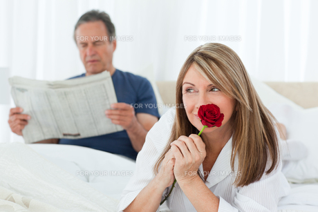 Happy woman smelling her rose while her husband is reading a newspaperの素材 [FYI00483579]