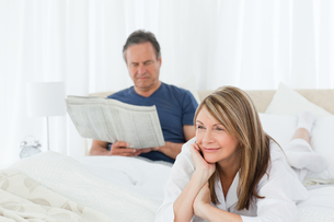 Woman smiling while her husband is readingの写真素材 [FYI00483580]