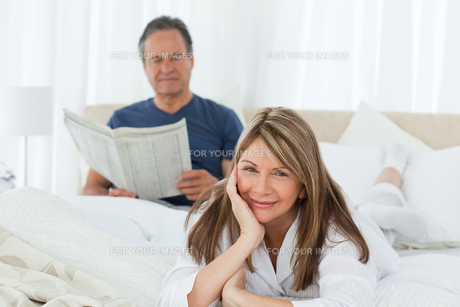 Smiling woman looking at the camera  while her husband is readingの写真素材 [FYI00483581]