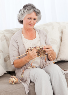 Senior woman knitting on her sofaの写真素材 [FYI00483594]