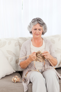 Senior woman knitting on her sofaの写真素材 [FYI00483595]