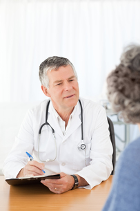A senior doctor talking with his patientの素材 [FYI00483607]
