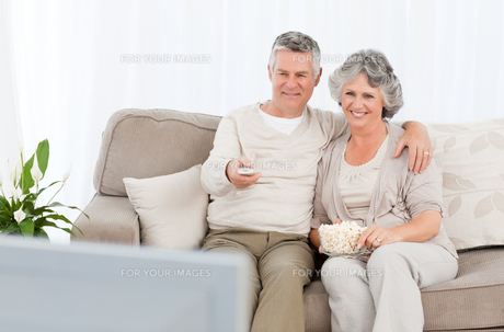 Mature couple watching tv in their living roomの写真素材 [FYI00483614]