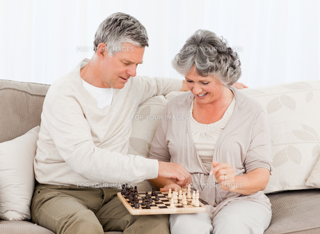 Couple playing chess on their sofaの写真素材 [FYI00483616]