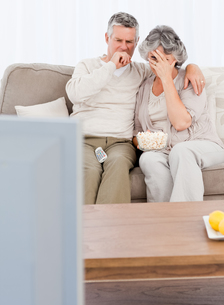 Mature couple watching tv in their living roomの写真素材 [FYI00483617]