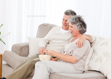 Mature couple watching tv in their living roomの写真素材 [FYI00483618]