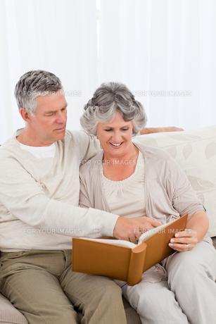 Senior couple looking at their photo albumの写真素材 [FYI00483619]