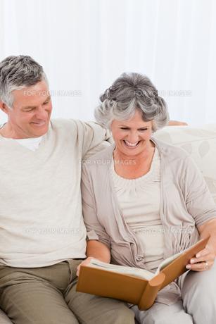 Senior couple looking at their photo albumの写真素材 [FYI00483621]