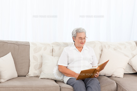 Woman looking at her photo albumの写真素材 [FYI00483623]