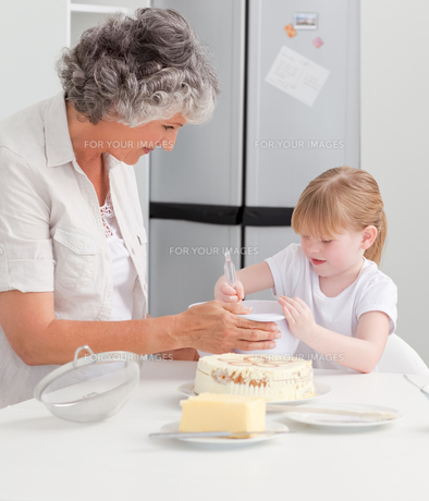Girl baking with her grandmother at homeの素材 [FYI00483651]