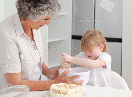 Girl baking with her grandmother at homeの素材 [FYI00483654]