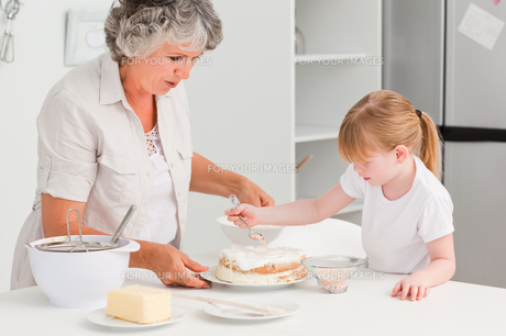 Girl baking with her grandmother at homeの素材 [FYI00483656]