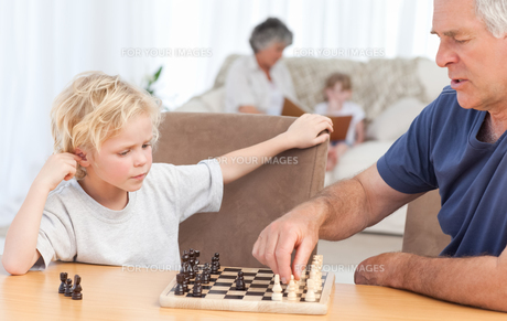 Young boy playing chess with his grandfatherの素材 [FYI00483665]