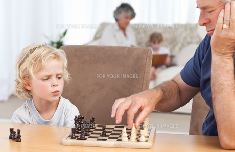 Young boy playing chess with his grandfatherの素材 [FYI00483666]