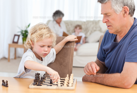 Young boy playing chess with his grandfatherの写真素材 [FYI00483667]