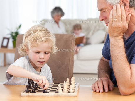 Young boy playing chess with his grandfatherの写真素材 [FYI00483669]