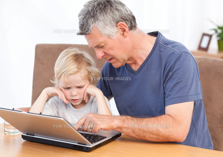 Lovely boy and his grandfather looking at their laptopの写真素材 [FYI00483672]