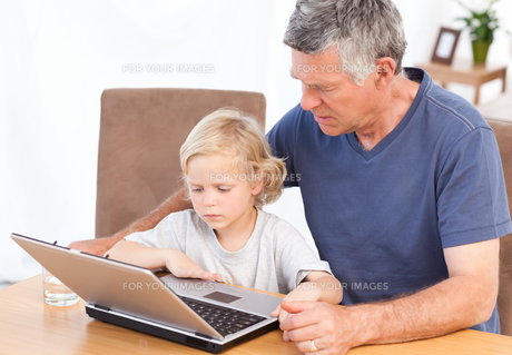 Lovely boy and his grandfather looking at their laptopの写真素材 [FYI00483674]