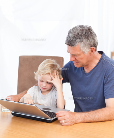 Lovely boy and his grandfather looking at their laptopの写真素材 [FYI00483676]