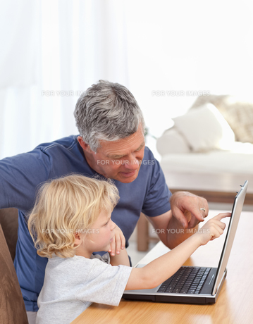 Lovely boy and his grandfather looking at their laptopの写真素材 [FYI00483677]