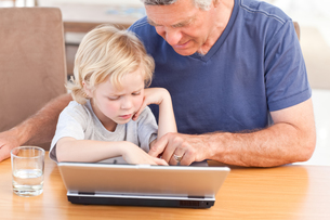 Lovely boy and his grandfather looking at their laptopの写真素材 [FYI00483678]