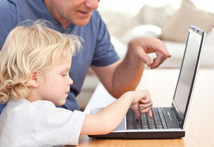 Lovely boy and his grandfather looking at their laptopの写真素材 [FYI00483679]