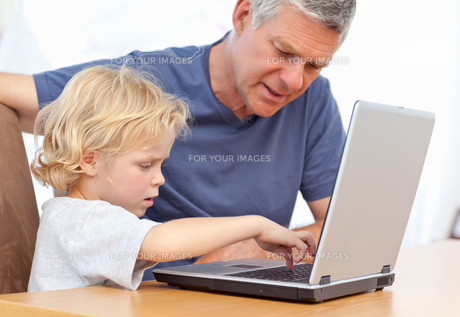 Lovely boy and his grandfather looking at their laptopの写真素材 [FYI00483683]