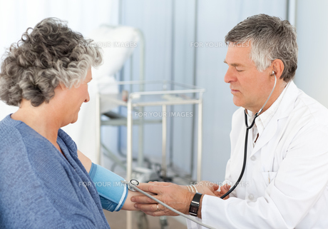 A senior doctor taking the blood pressure of his patientの素材 [FYI00483684]