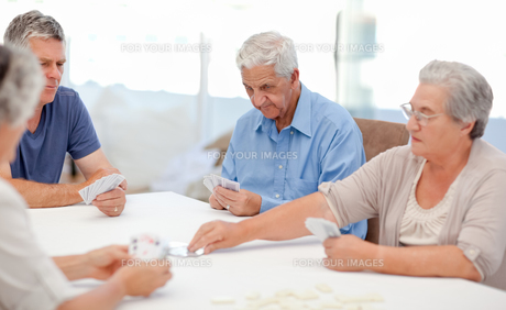 Retired people playing cards togetherの写真素材 [FYI00483698]