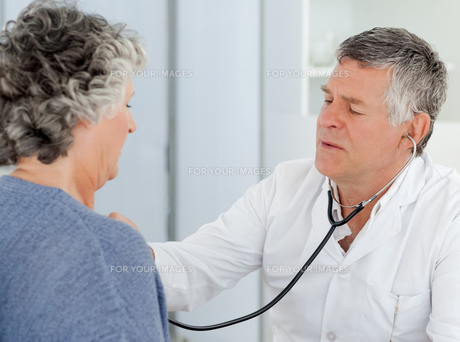 A senior doctor doing a checkup to his patientの素材 [FYI00483703]