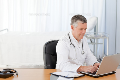 A senior doctor working on his laptop in his officeの写真素材 [FYI00483706]
