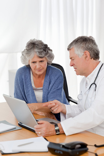 A senior doctor with his patient looking at the laptopの素材 [FYI00483708]