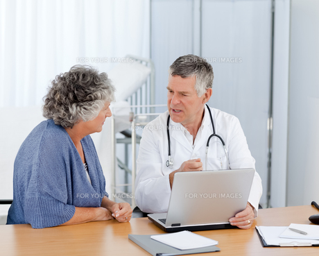 A senior doctor with his patient looking at the laptopの素材 [FYI00483709]