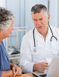 A senior doctor with his patient looking at the laptopの素材 [FYI00483710]