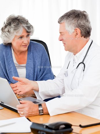 A senior doctor with his patient looking at the laptopの素材 [FYI00483711]